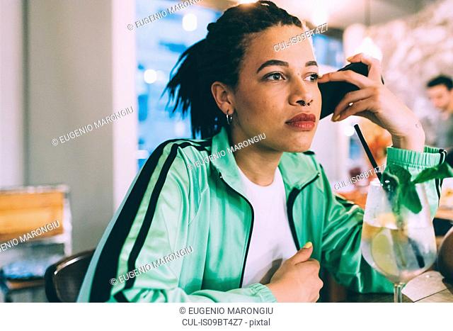 Woman listening to message on mobile while having drink in bar