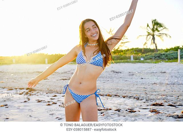Latin beautiful bikini girl happy in Caribbean beach sunset