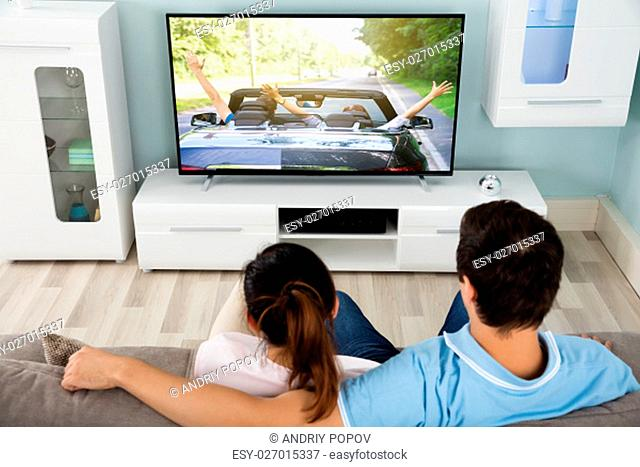 Young Couple On Sofa Watching Movie On Television Together At Home