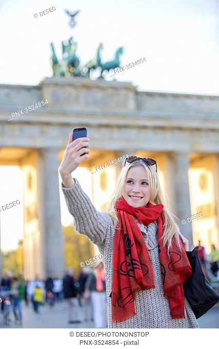 Pretty blonde woman taking a selfie in front of the Brandenburg Gate in Berlin, Germany