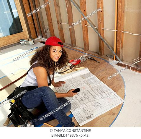 Hispanic woman looking at blueprints