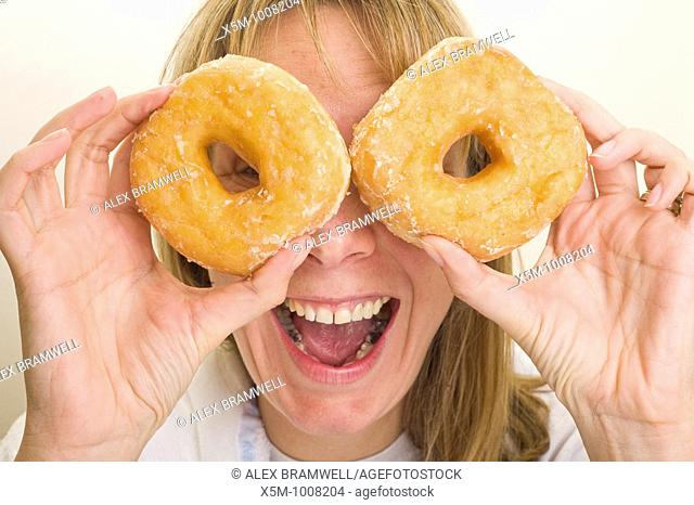 Woman holding donuts up in front of her eyes