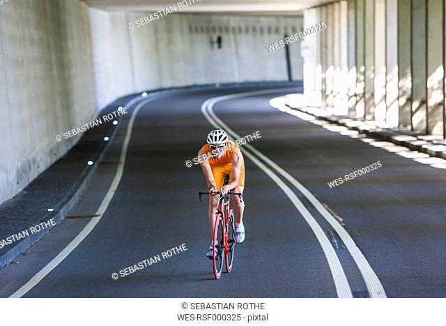 Racing biker riding through a tunnel