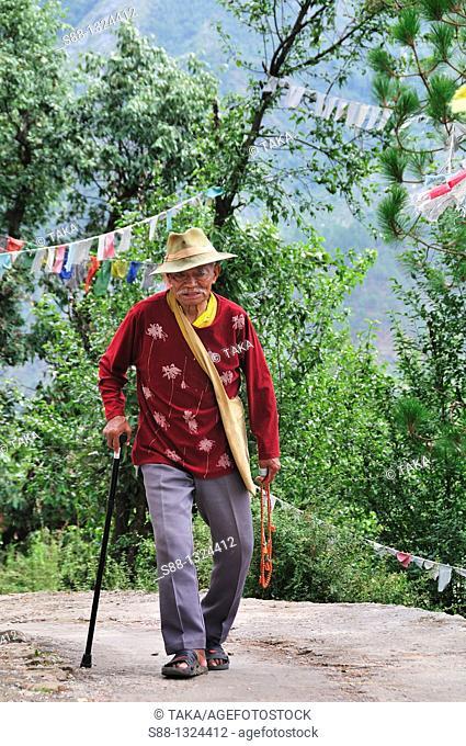 Old man walking through peaceful little pass