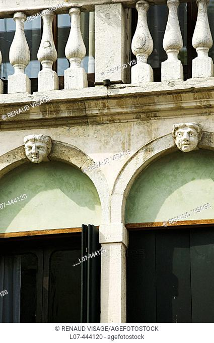 Detail of façade with sculpted heads. Venice. Italy