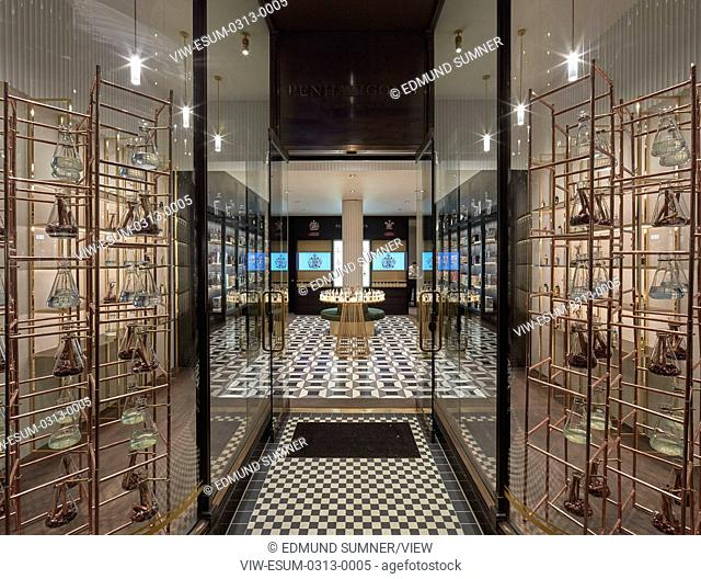 In this store blackened oak shelving is dissolved into a framework enabling a display that both suited the deep and narrow inter