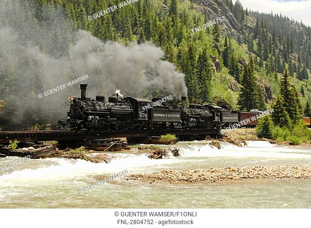 Train moving on track passing through river, Colorado, USA