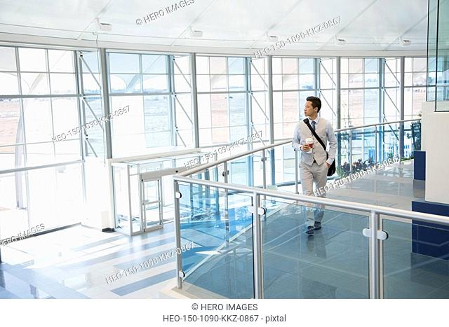 Businessman with coffee in modern office atrium