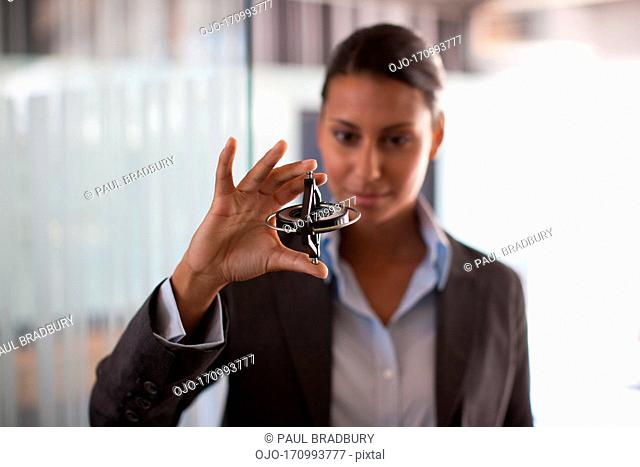 Businesswoman holding gyroscope in office