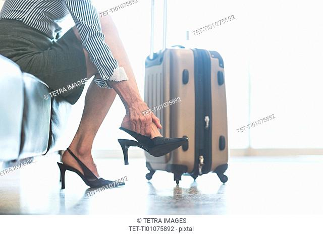 Businesswoman at the airport adjusting shoe