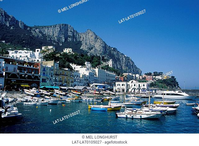 View from sea. Boats. Town,houses,harbour. Mountains,rock formations