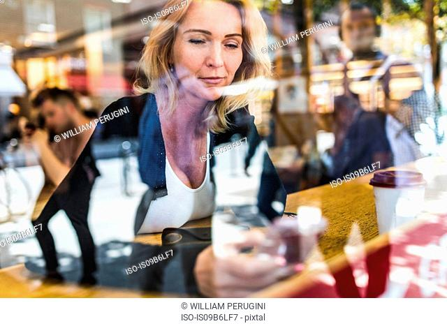 Window view of woman in cafe looking at smartphone