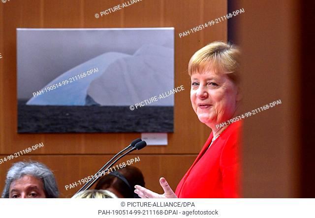 14 May 2019, Berlin: Chancellor Angela Merkel (CDU, l) speaks at the 10th Petersberg Climate Dialogue, in the background you can see a photo of an iceberg