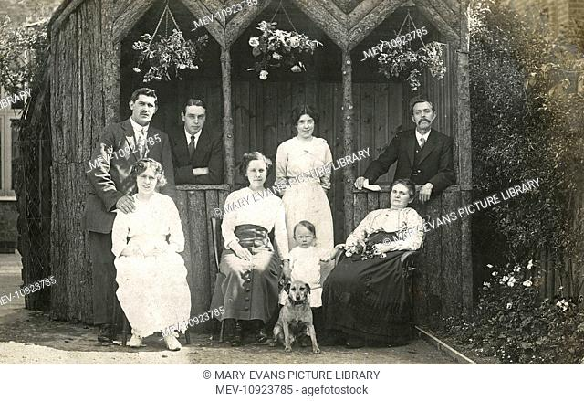 Eight people with a dog in a garden