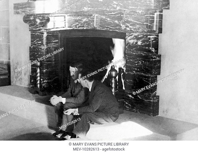 Adolf Hitler and Joseph Goebbels sit by a large fireplace, deep in conversation, at the Berghof, near Berchtesgarden in the Bavarian Alps