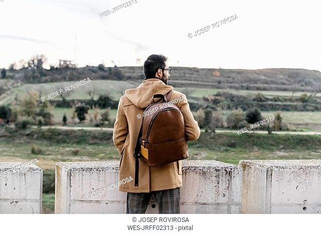 Spain, Igualada, rear view of man with backpack standing at concrete wall