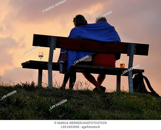 Couple sitting on a dyke, island Neuwerk, Elbe estuary, North Sea, Hamburg, Germany