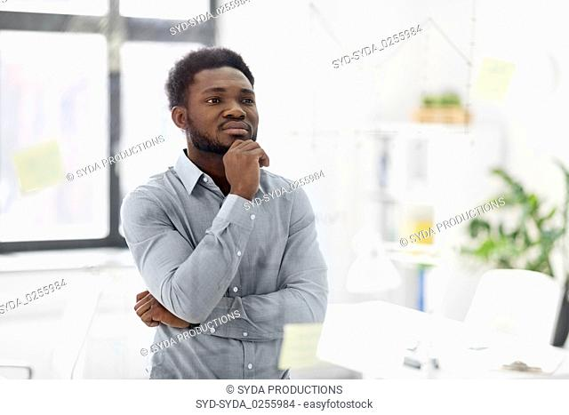 businessman looking at glass board at office