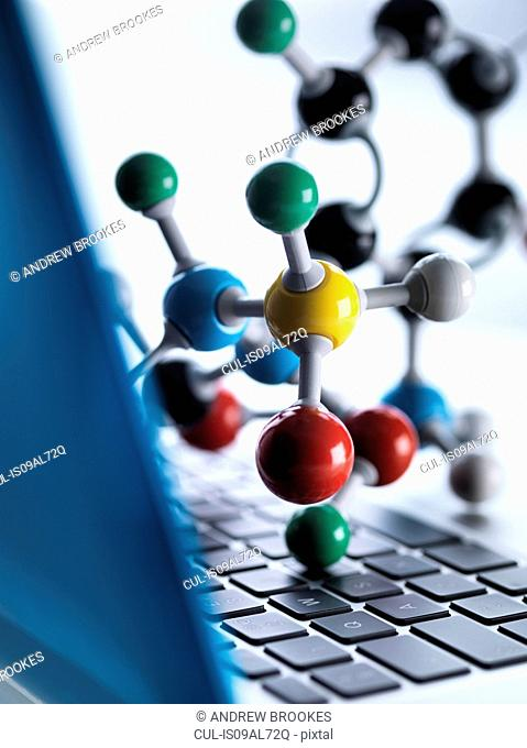 Close up of molecular model sitting on top of lap top computer keyboard to illustrate science education and computer aided research