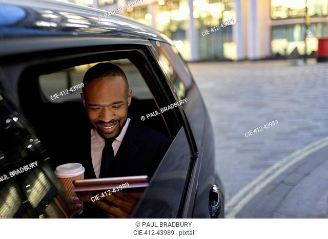 Businessman drinking coffee and using digital tablet in crowdsourced taxi