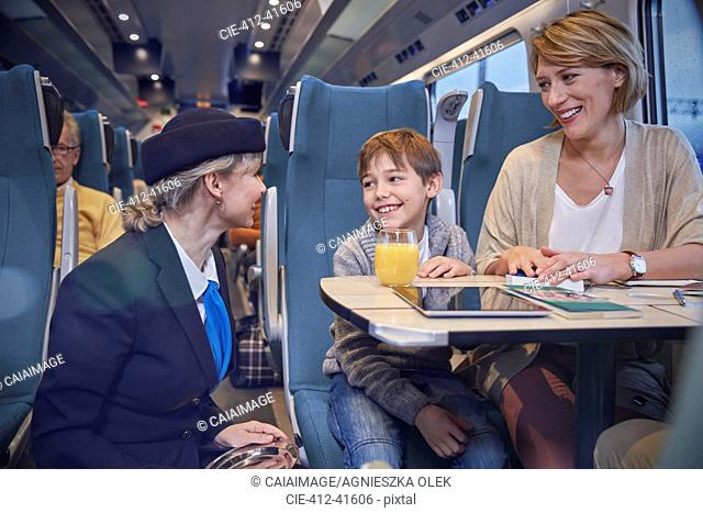Attendant talking with mother and son on passenger train