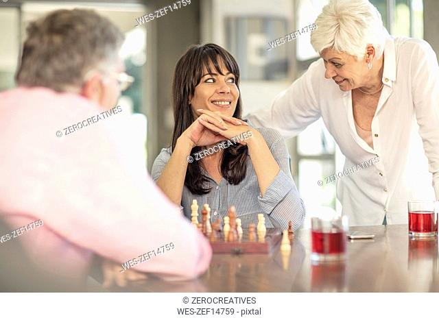 Senior couple playing chess with daughter at home