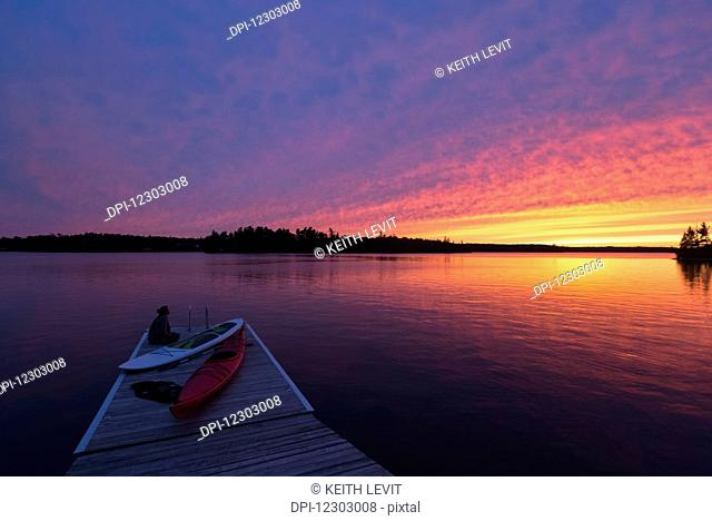 A young woman sits at the end of the dock with kayaks watching the sun set over a lake; Ontario, Canada
