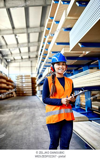 Smiling female worker with ear muffs and clipboard in factory warehouse