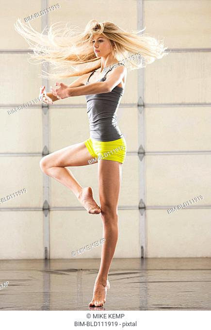 Caucasian dancer practicing in studio