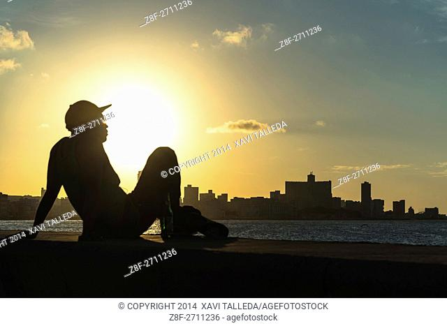 A Cuban man watching the sunset from the Malecón
