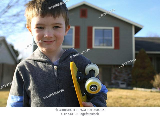 Boy, age five, looking at camera with skateboard in front of home