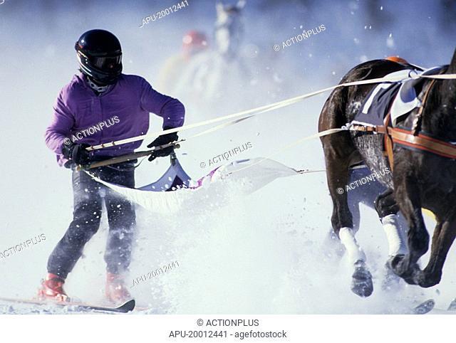 Jockeys sled behinds their horses at winter ice racing
