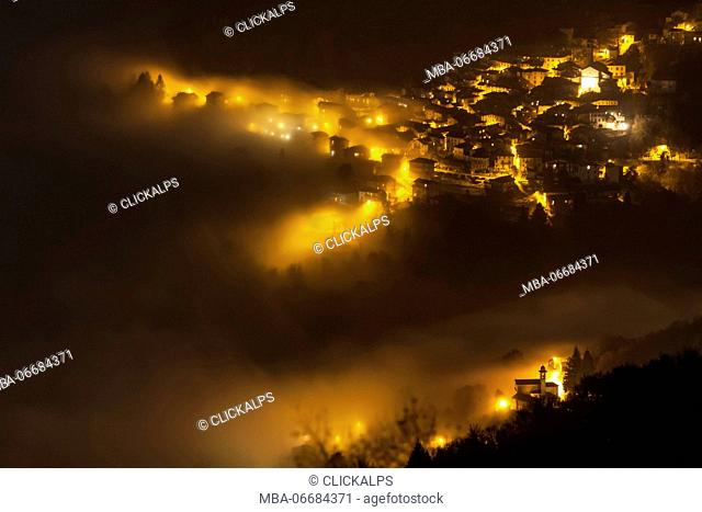 Molina of Palanzo village on Comolake by nigth surrounded by the fog, from Monte Boletto, Province of Como, Lombardy, Italy