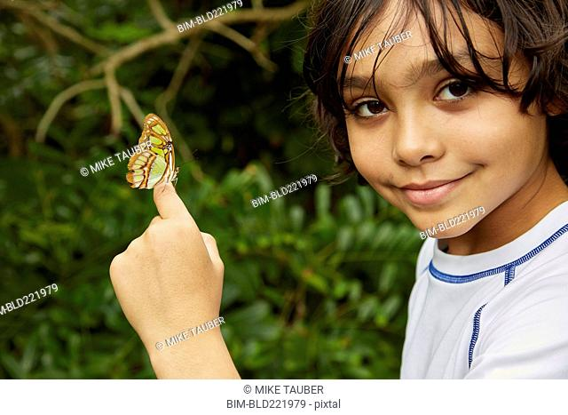 Mixed race boy holding butterfly