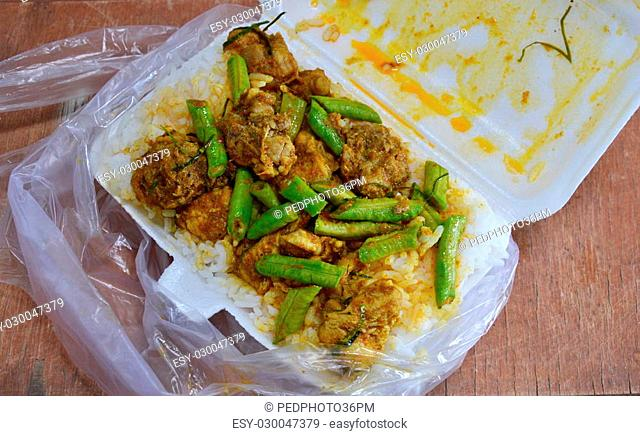 stir-fried spicy curry with crispy chicken on rice in foam box