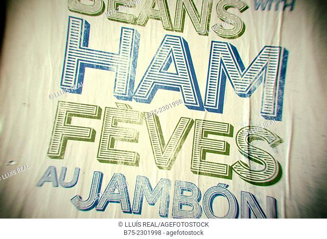 Closeup of a part of an old poster with the text: Beans with Ham, Feves au Jambon, in La Boqueria market, Las Ramblas, Barcelona, Catalonia, Spain, Europe