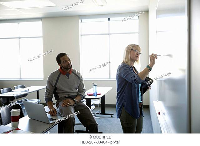 Professor and adult education student at whiteboard in classroom