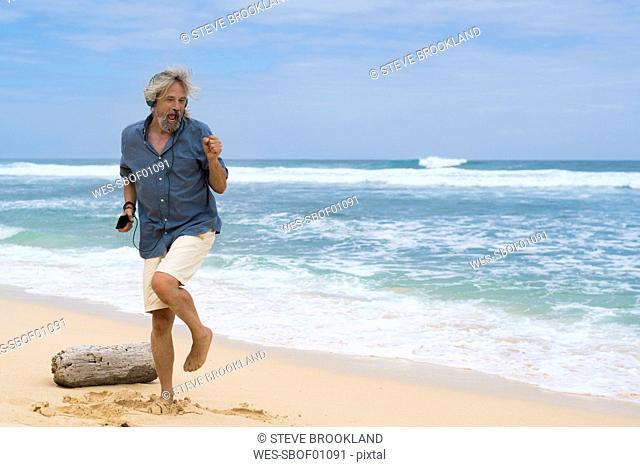 Handsome senior man with headphones dancing on the beach