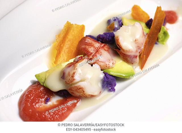 Lobster with sauce and vegetables on a white plate