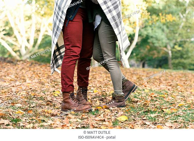 Waist down view of mid adult couple wrapped in blanket in park