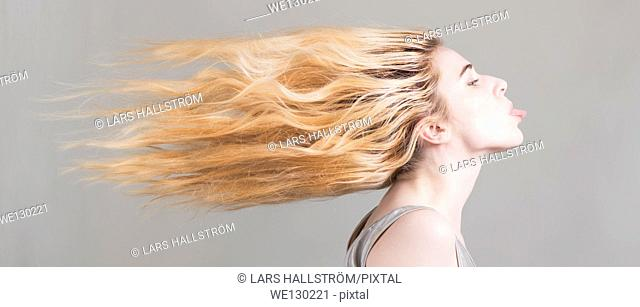 Blonde woman with long hair flying sticking her tongue out. Conceptual image of freedom, strong attitude and personality