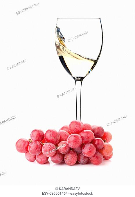 Splashing white wine in a glass and grapes. Isolated on white background