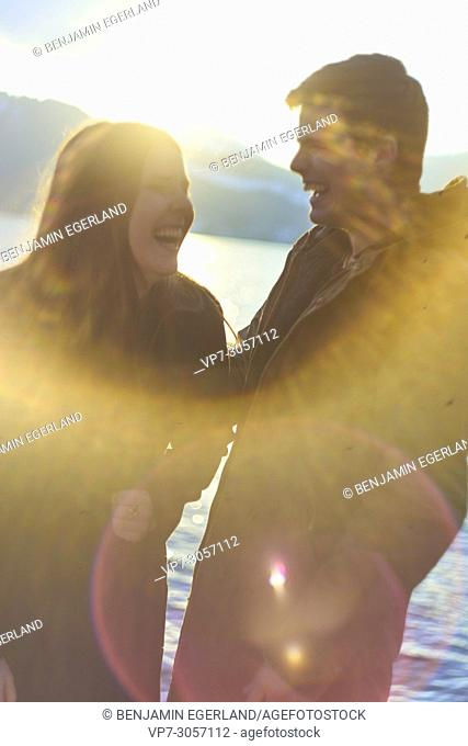 Tegernsee, Germany, playful couple next to lake, sunny weather, winter clothes