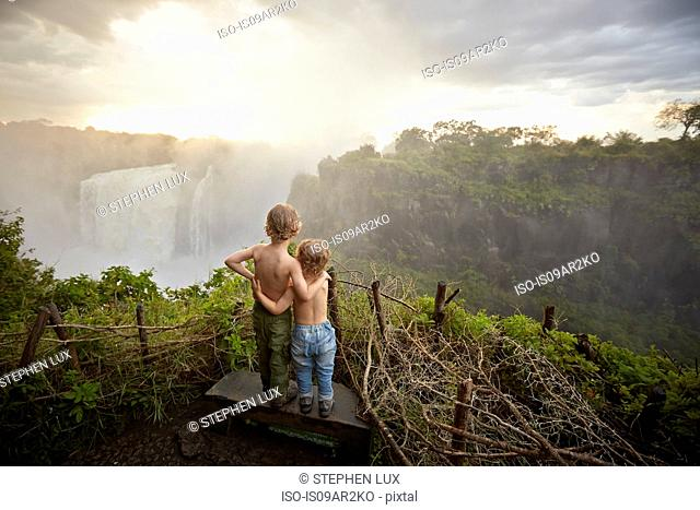 Two young boys standing on ledge admiring the view, rear view, Victoria Falls, Livingstone, Zimbabwe