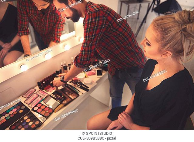 Male make up artist selecting make up for photo shoot