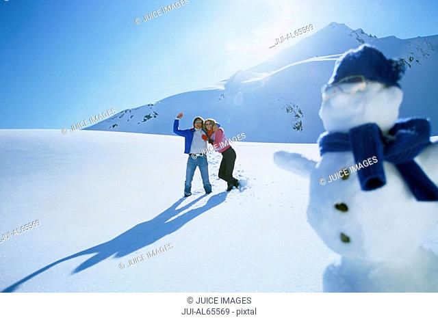 Young couple waving to snowman