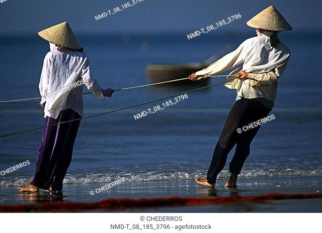 Rear view of two fishermen pulling a fishing net from the sea, Vietnam