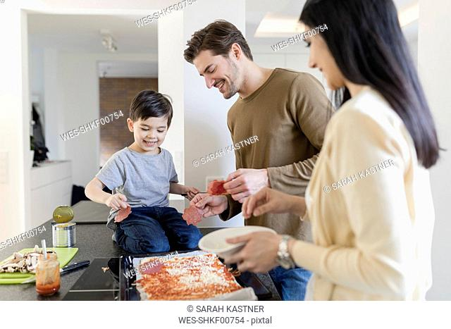 Family preparing pizza in kitchen together