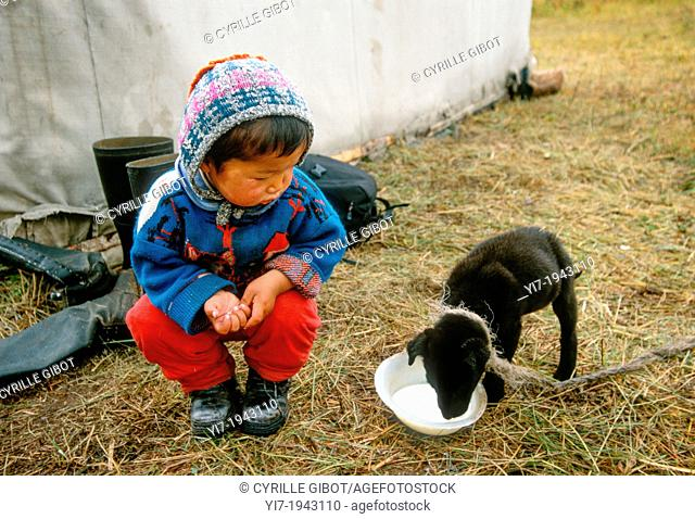 Baby boy looking at a puppy drinking milk, Kyrgyzstan