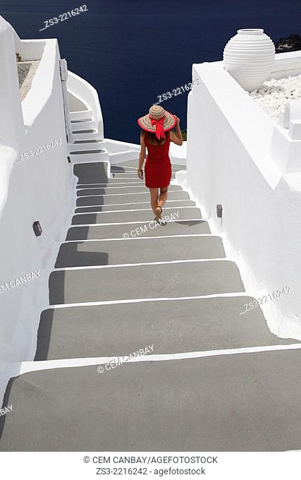Woman walking down the stairs in Oia town, Santorini, Cyclades Islands, Greek Islands, Greece, Europe